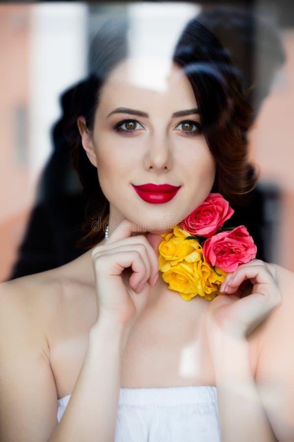 Porträt der schönen jungen Frau, die nahe dem Fenster und dem L steht lizenzfreies stockfoto