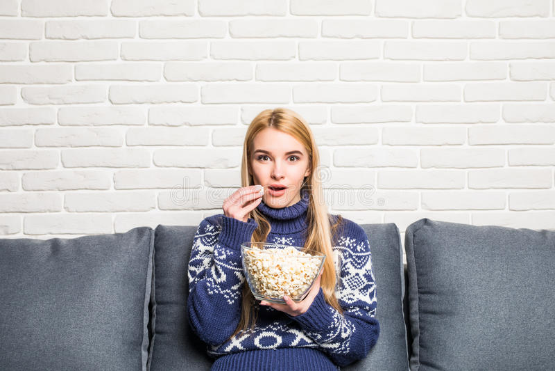 Porträt der schönen jungen Frau, die Popcorn beim Aufpassen des Films im Wohnzimmer isst stockbilder