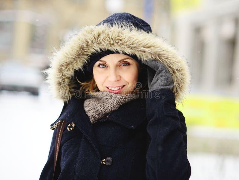 Porträt der schönen jungen Frau in einem Wintermantel mit Pelzhaube lizenzfreies stockbild