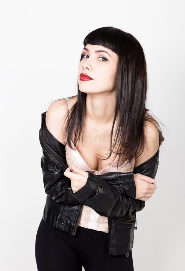 Porträt der schönen jungen Frau in einer Lederjacke, stehend mit bloßen Schultern gedreht Aufstellung an der Kamera lizenzfreie stockfotografie