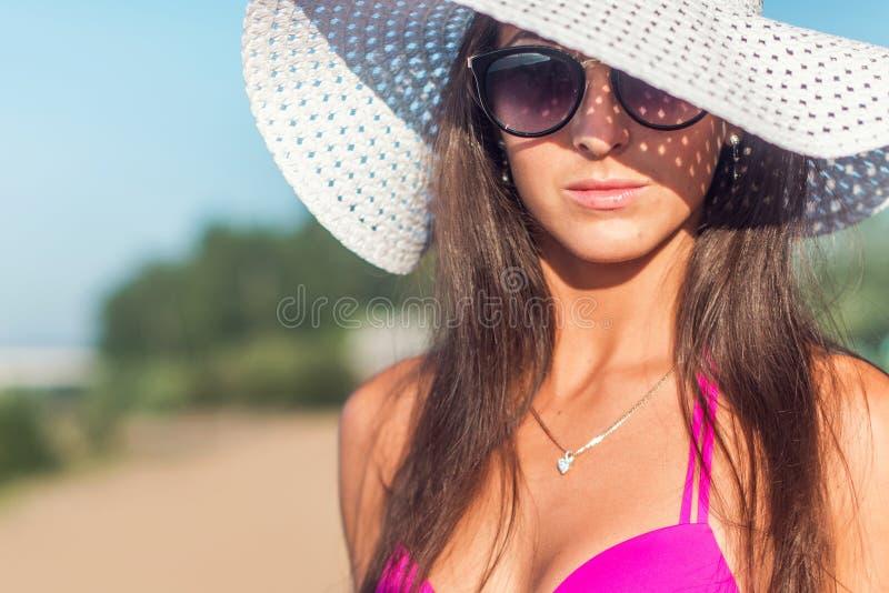 Porträt der schönen jungen Frau im Hut, der im Bikini auf dem Strand aufwirft stockfotografie