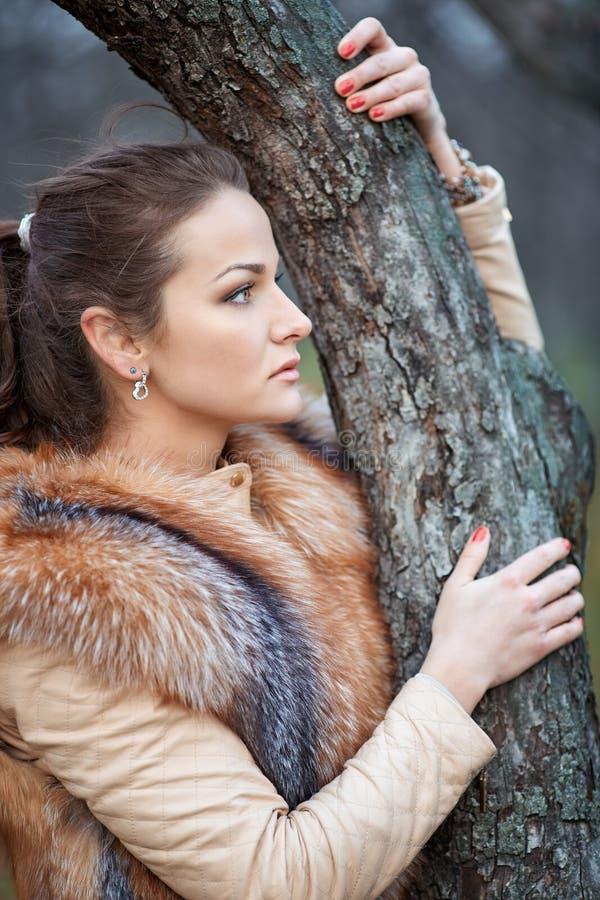 Porträt der schönen jungen Frau im Pelz im Park lizenzfreie stockbilder