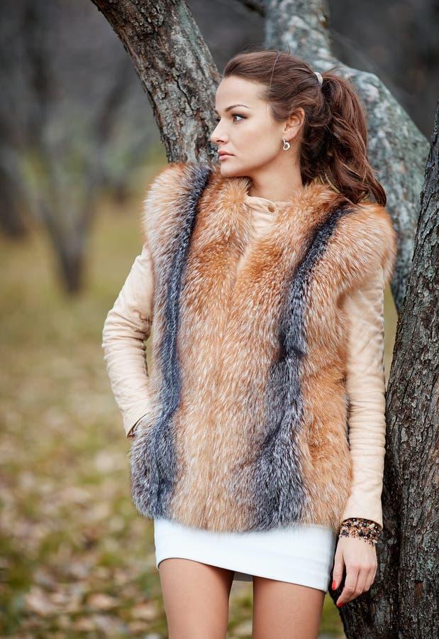 Porträt der schönen jungen Frau im Pelz im Park lizenzfreies stockbild
