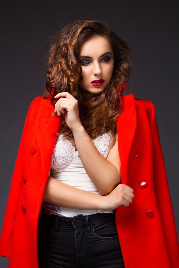 Porträt der schönen jungen Frau im roten Mantel und in den schwarzen Jeans lizenzfreie stockfotos