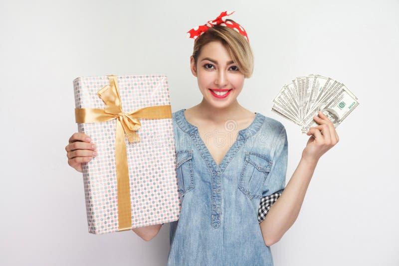 Porträt der schönen jungen Frau im zufälligen blauen Denimhemd mit Make-up und roter Stirnbandstellung, Geschenkbox und Fan zeige stockbild