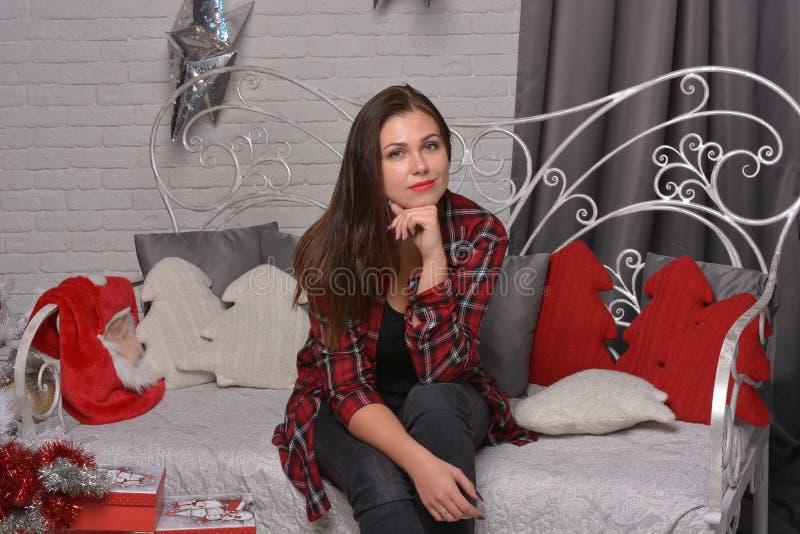 Porträt der schönen jungen Frau ist naher Weihnachtsbaum stockbild