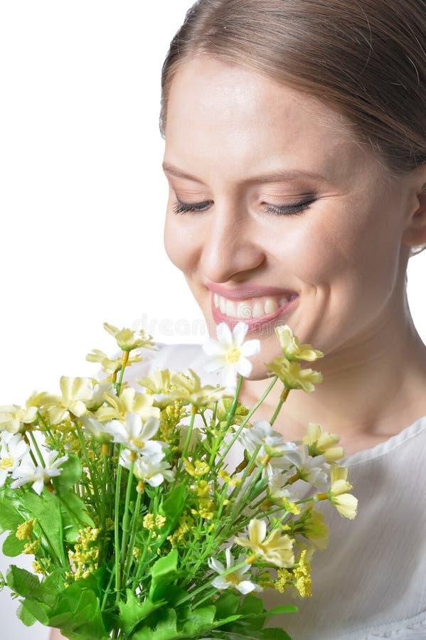 Porträt der schönen jungen Frau mit Blumen auf weißem Hintergrund lizenzfreie stockfotos
