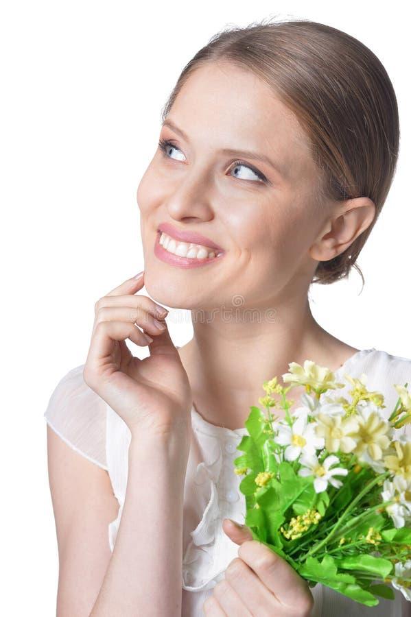Porträt der schönen jungen Frau mit Blumen auf weißem Hintergrund lizenzfreie stockbilder