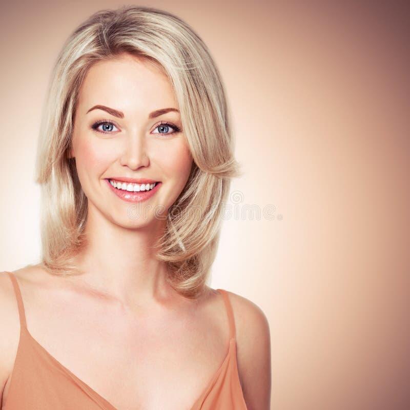 Porträt der schönen jungen Frau mit dem Lächeln, das betrachtet, kam lizenzfreie stockfotos