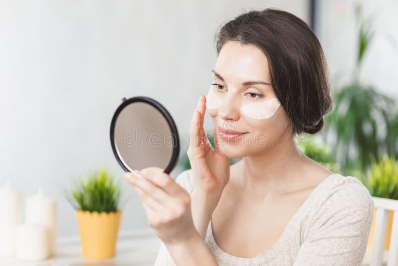 Porträt der schönen jungen Frau mit dem natürlichen Make-up, das Weiß unter Augenklappe-Schönheits-Maske auf Gesicht anwendet Mäd stockbild