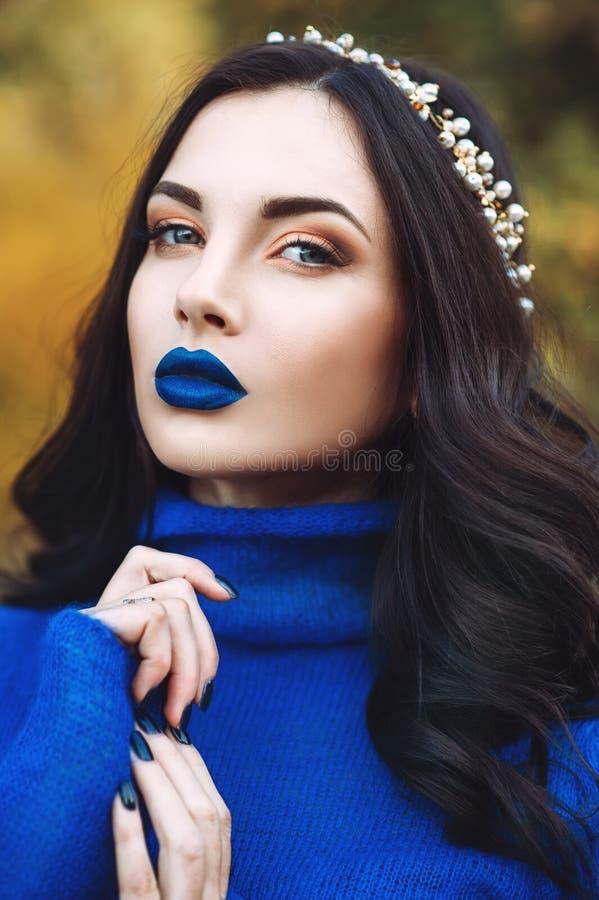Porträt der schönen jungen Frau mit den blauen Lippen und blauer Strickjacke mit Zusatz auf ihrem Kopf im Park stockfotos