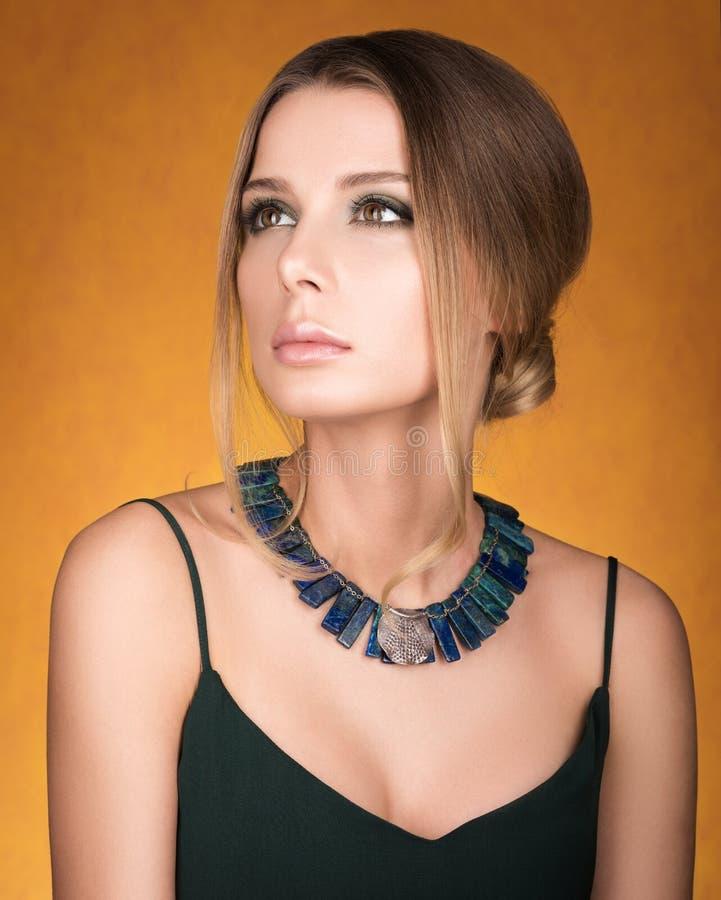 Porträt der schönen jungen Frau mit einer Halskette auf ihrem Hals Frisur und Make-up stockfotografie