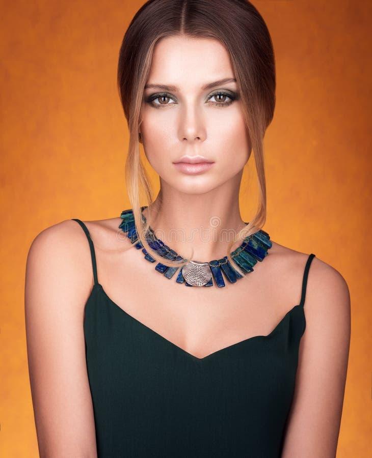 Porträt der schönen jungen Frau mit einer Halskette auf ihrem Hals Haar und Make-up lizenzfreie stockfotos