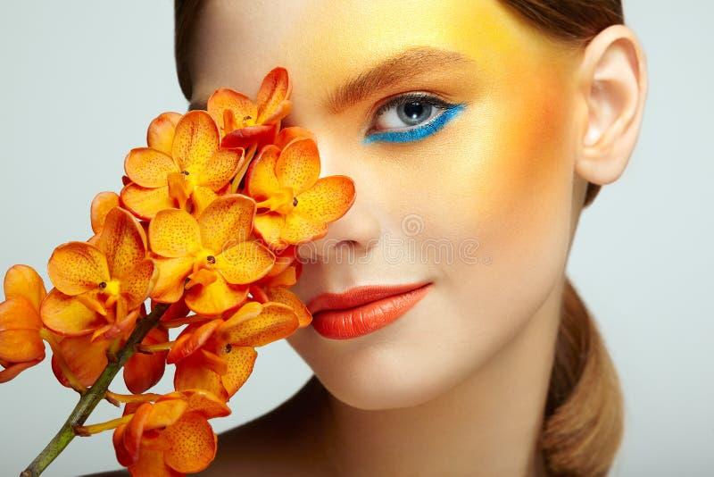 Porträt der schönen jungen Frau mit Orchidee lizenzfreies stockfoto