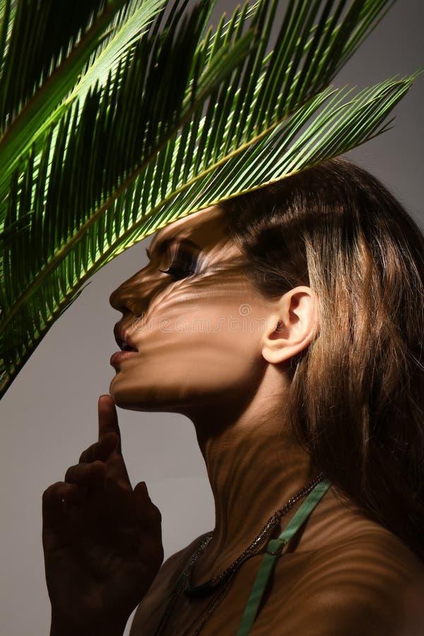 Porträt der schönen jungen Frau mit Palmblättern lizenzfreies stockfoto