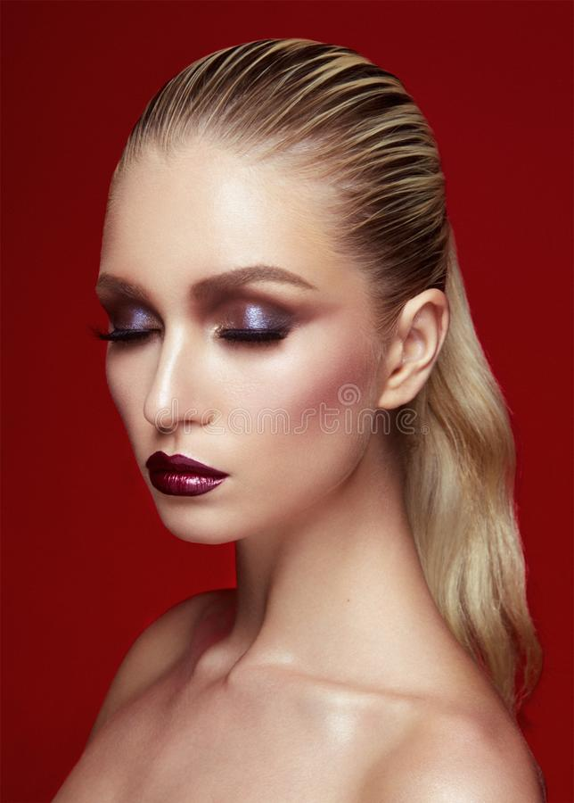 Porträt der schönen jungen Frau mit perfektem Make-up Geschlossene Augen modellieren, wenn das Haar auf Burgunder-Hintergrund ger lizenzfreie stockfotografie