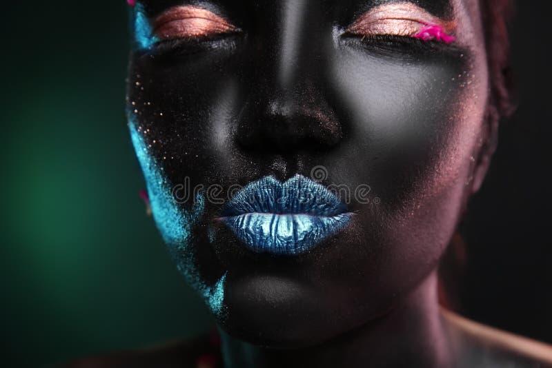 Porträt der schönen jungen Frau mit surrealem Make-up auf dunklem Hintergrund, Nahaufnahme lizenzfreies stockfoto