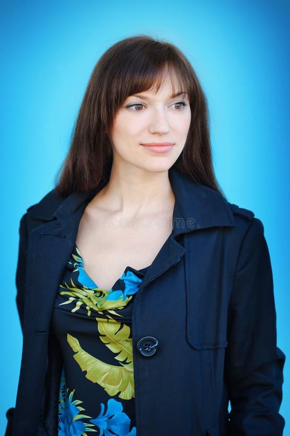Porträt der schönen jungen glücklichen lächelnden Frau, über blauem Hintergrund lizenzfreie stockfotos