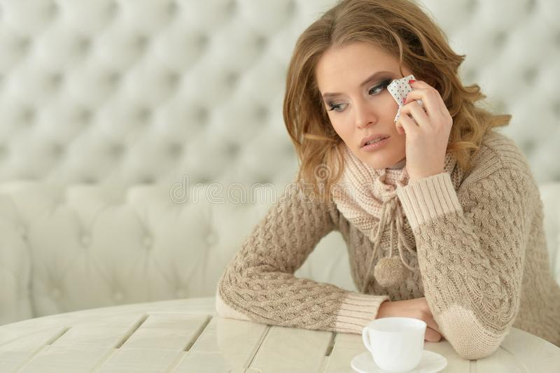 Porträt der schönen jungen traurigen Frau, die zu Hause schreit stockfoto