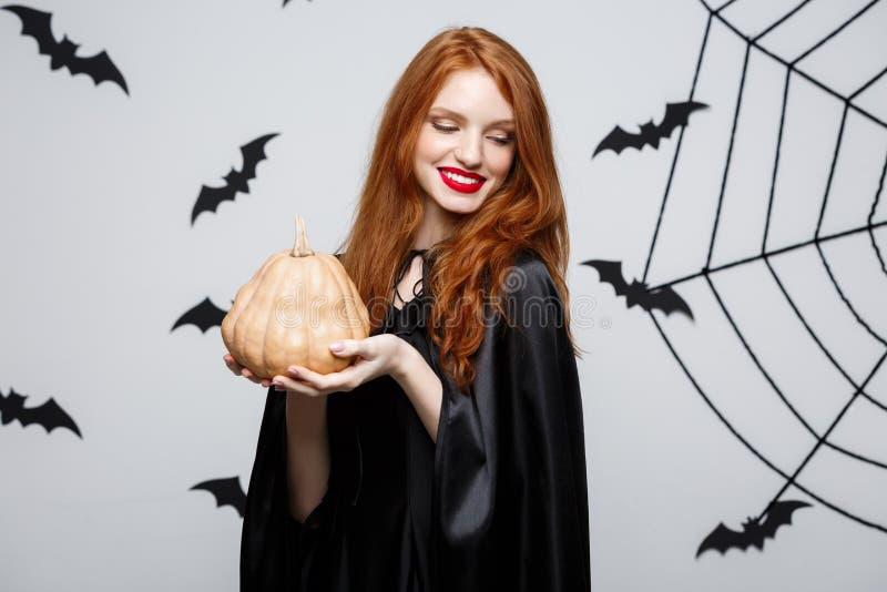 Porträt der schönen kaukasischen Hexe, die Kürbis für das Feiern von Halloween hält stockfoto