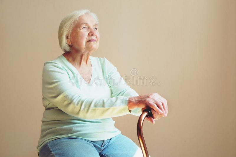 Porträt der schönen lächelnden älteren Frau mit gehendem Stock auf hellem Hintergrund zu Hause lizenzfreies stockbild