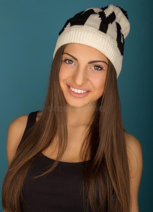 Porträt der schönen lächelnden braunhaarigen Frau in Winterhut a lizenzfreie stockfotos