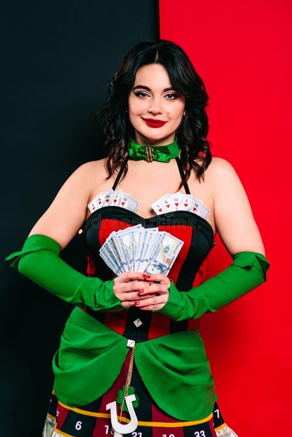 Porträt der schönen lächelnden Brunettefrau mit bilden im Rot- und Schwarzkleid mit Karten stockfotografie