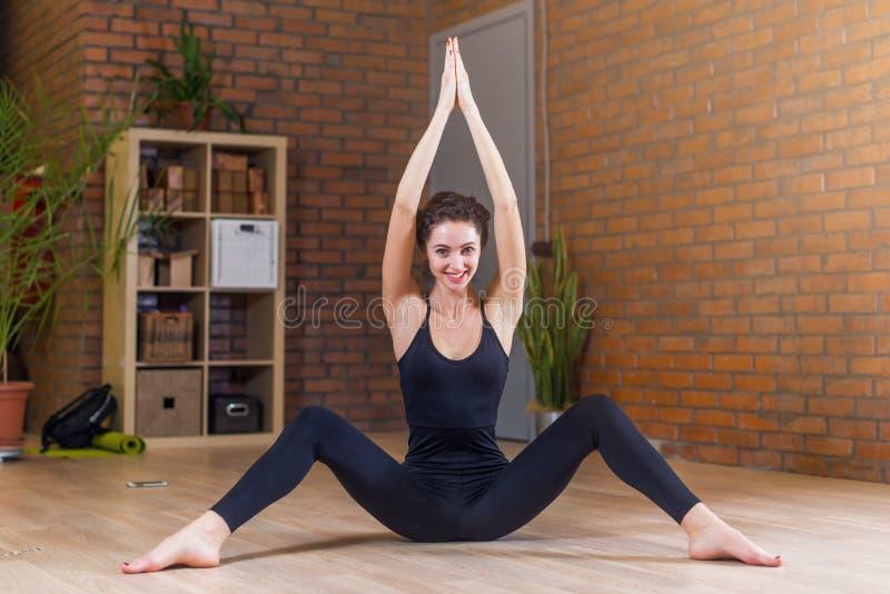 Porträt der schönen lächelnden Frau, die die Übung ausdehnend sitzt auf Boden mit ihrer Beinverbreitung und -armen oben angehoben stockbild