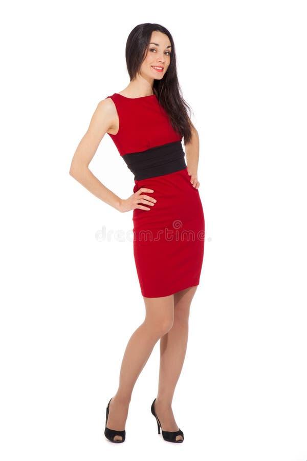Porträt der schönen lächelnden Frau, die rotes Kleid und Schwarzes trägt stockbild