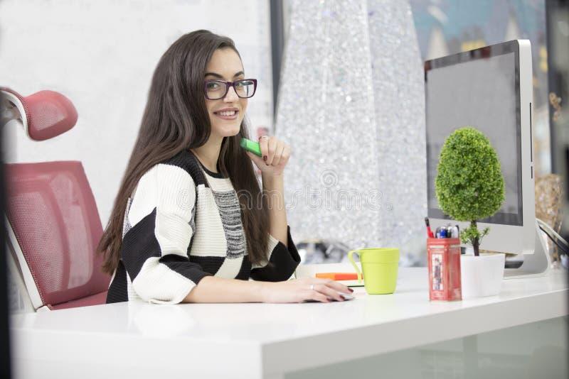 Porträt der schönen lächelnden jungen Brunettegeschäftsfrau, die am hellen modernen Arbeitsplatz sitzt und auf Laptop schreibt stockbilder