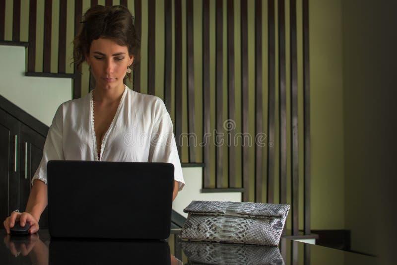 Porträt der schönen lächelnden jungen Brunettegeschäftsfrau, die am hellen modernen Arbeitsplatz sitzt und auf Laptop schreibt Na stockbilder