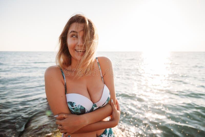 Porträt der schönen lächelnden jungen Frau im Bikini auf Strand Weibliches Modell, das im Badeanzug auf Seeufer aufwirft Sommerfe stockfotos