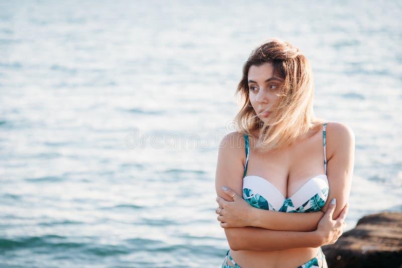Porträt der schönen lächelnden jungen Frau im Bikini auf Strand Weibliches Modell, das im Badeanzug auf Seeufer aufwirft Sommerfe stockbild