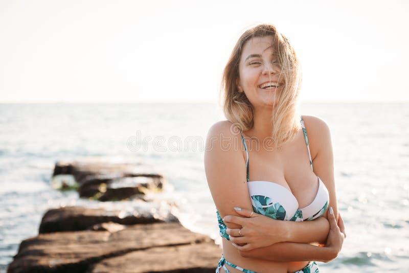 Porträt der schönen lächelnden jungen Frau im Bikini auf Strand Weibliches Modell, das im Badeanzug auf Seeufer aufwirft Sommerfe lizenzfreie stockbilder
