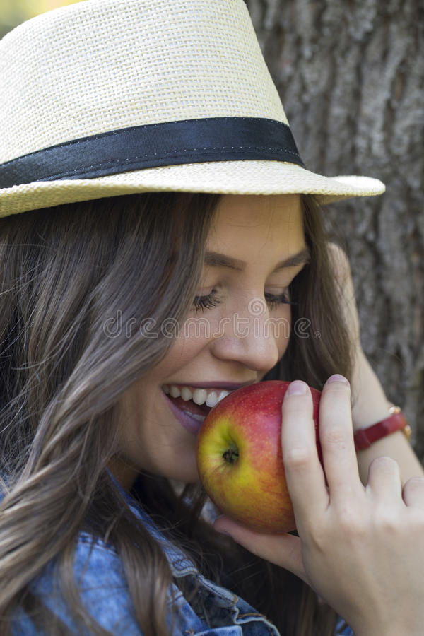 Porträt der schönen lächelnden jungen Frau mit Hut Apfel essend stockbild
