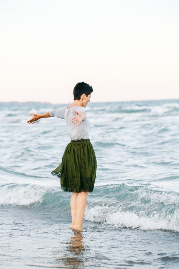 Porträt der schönen lächelnden lachenden kaukasischen Brunettefrau mit dem kurzen Haar im grauen Hemd, Ballettröckchentulle-Rock  stockbilder