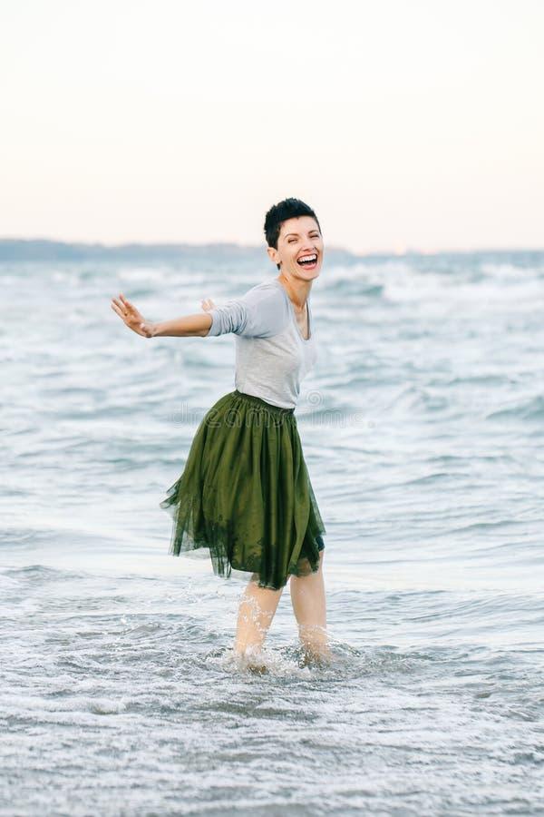 Porträt der schönen lächelnden lachenden kaukasischen Brunettefrau mit dem kurzen Haar im grauen Hemd, Ballettröckchentulle-Rock  lizenzfreie stockfotografie