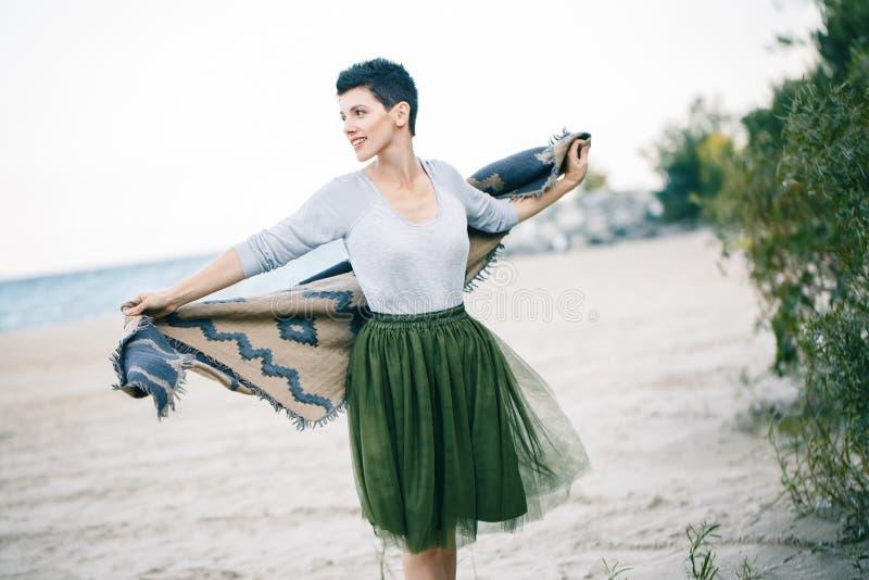 Porträt der schönen lächelnden lachenden kaukasischen Brunettefrau mit dem kurzen Haar im grauen Hemd, Ballettröckchentulle-Rock  lizenzfreies stockbild