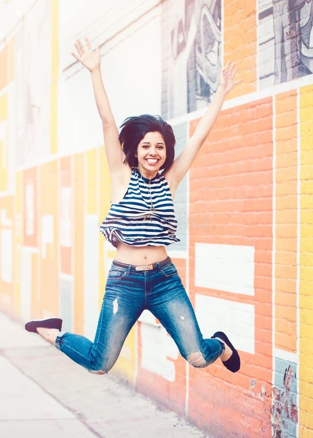 Porträt der schönen lächelnden lachenden lateinischen hispanischen Mädchenfrau des jungen Hippies, die oben in einer Luft springt stockfotos