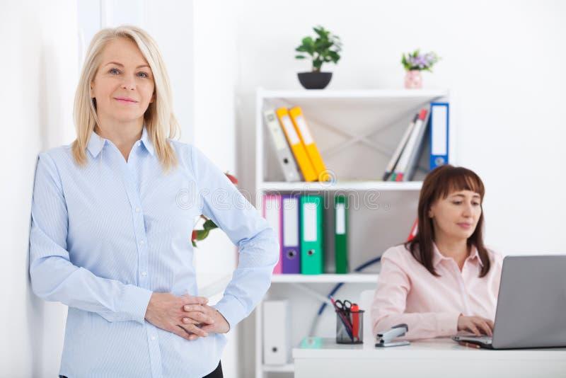 Porträt der schönen Mitte alterte Geschäftsfrau im Büro stockfotos