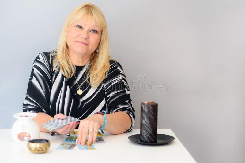 Porträt der schönen Mittelalterfrau sitzt nahe einem Wahrsagerschreibtisch mit Karten und Kerzen eines Tarocks stockfotografie