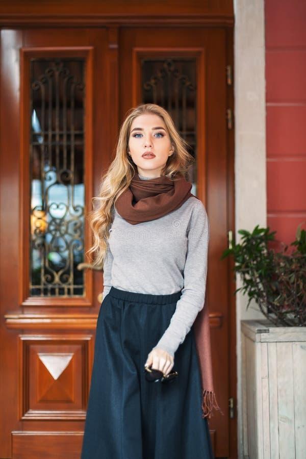 Porträt der schönen modernen jungen Frau, die auf der Straße aufwirft Dame, die Kamera betrachtet Weibliche Mode Taille oben stockbild
