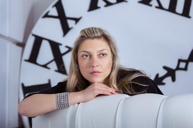 Porträt der schönen nachdenklichen Frau mit großer Uhr auf Hintergrund lizenzfreie stockbilder