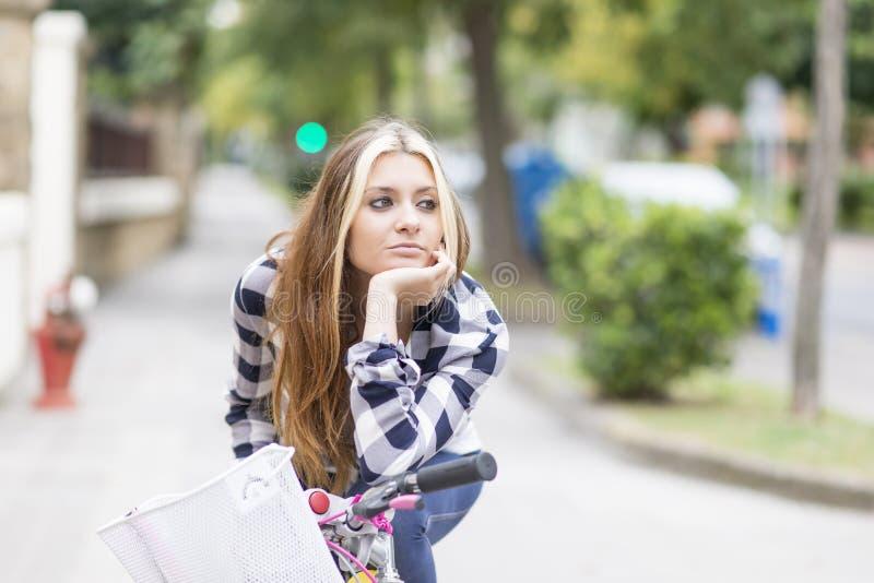 Porträt der schönen nachdenklichen jungen Frau mit Fahrrad in der Straße lizenzfreies stockfoto