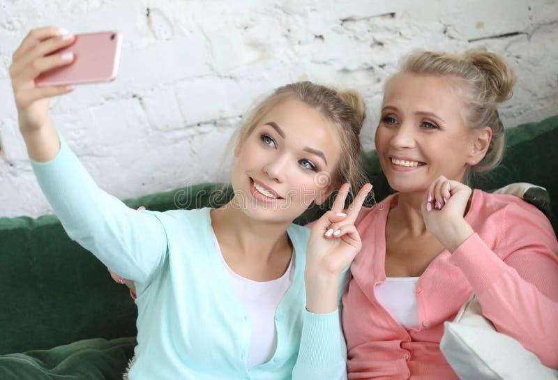 Porträt der schönen reifen ein selfie der unter Verwendung des intelligenten Telefons machenden und lächelnden Mutter und ihrer T lizenzfreie stockfotografie