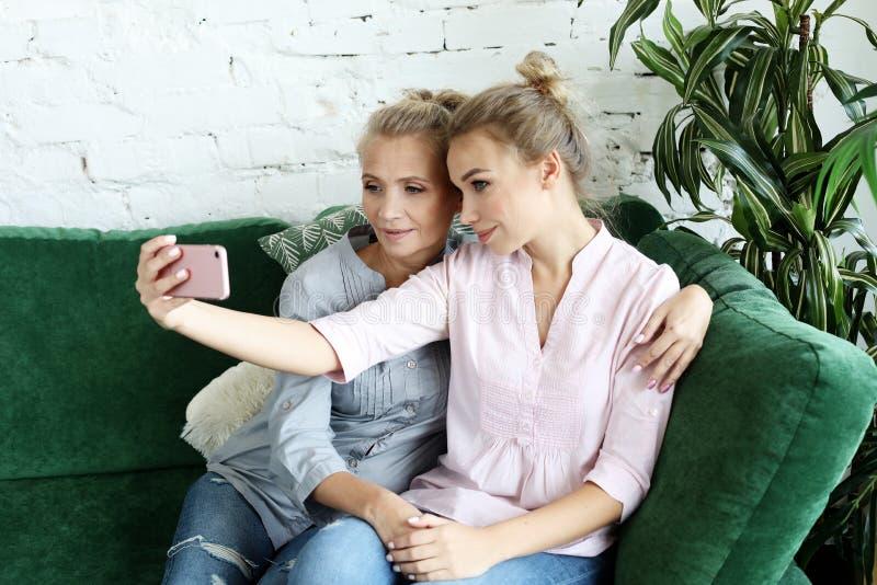 Porträt der schönen reifen ein selfie der unter Verwendung des intelligenten Telefons machenden und lächelnden Mutter und ihrer T stockfotografie