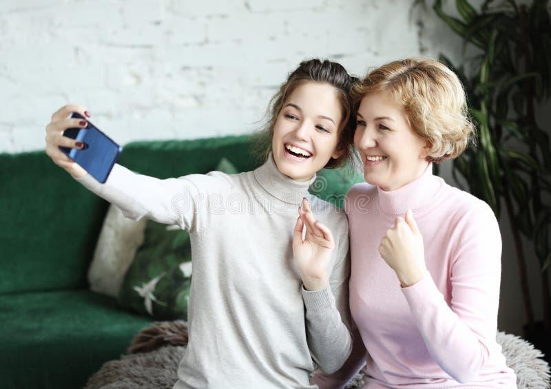 Porträt der schönen reifen ein selfie der unter Verwendung des intelligenten Telefons machenden und lächelnden Mutter und ihrer T lizenzfreies stockfoto