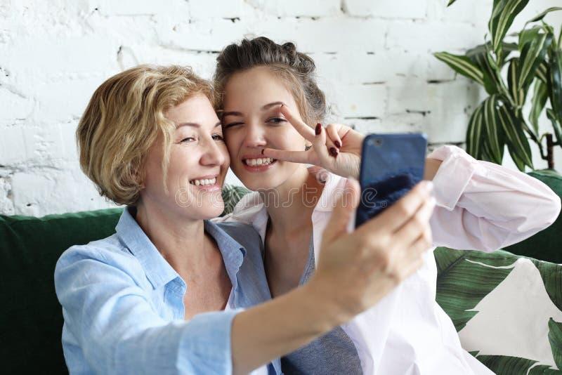 Porträt der schönen reifen ein selfie der unter Verwendung des intelligenten Telefons machenden und lächelnden Mutter und ihrer T lizenzfreie stockbilder