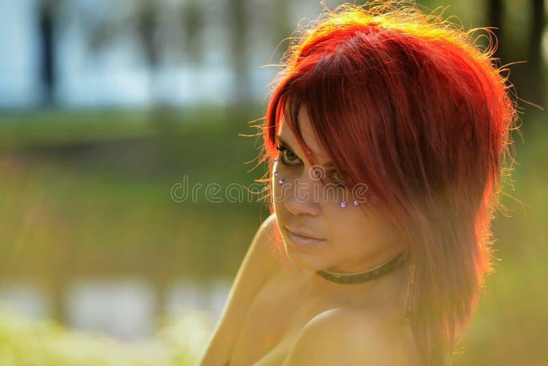 Porträt der schönen Rothaarfrau auf dem natürlichen Hintergrund mit Sonnenscheinhintergrundbeleuchtung stockfoto