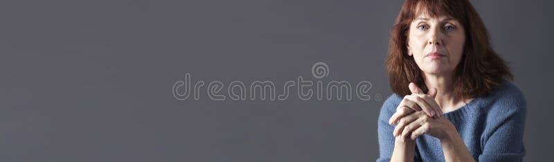 Porträt der schönen schauenden Frau 50s ruhige, graue Fahne lizenzfreie stockbilder